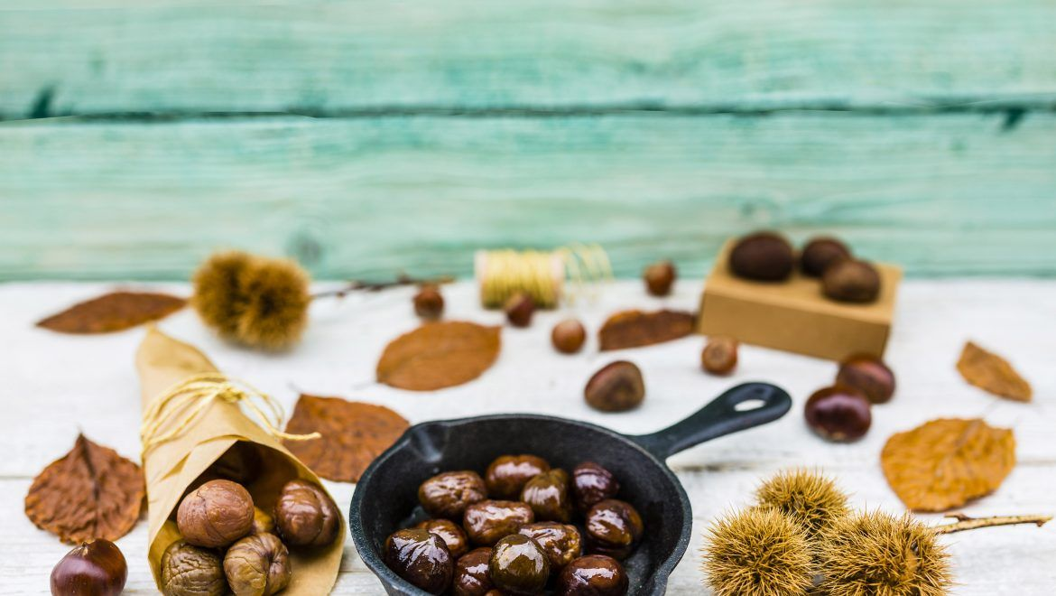 Delicious and hot roasted chestnuts on frying pan on old wooden